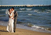 Groom hugging bride on the beach in front of the pier