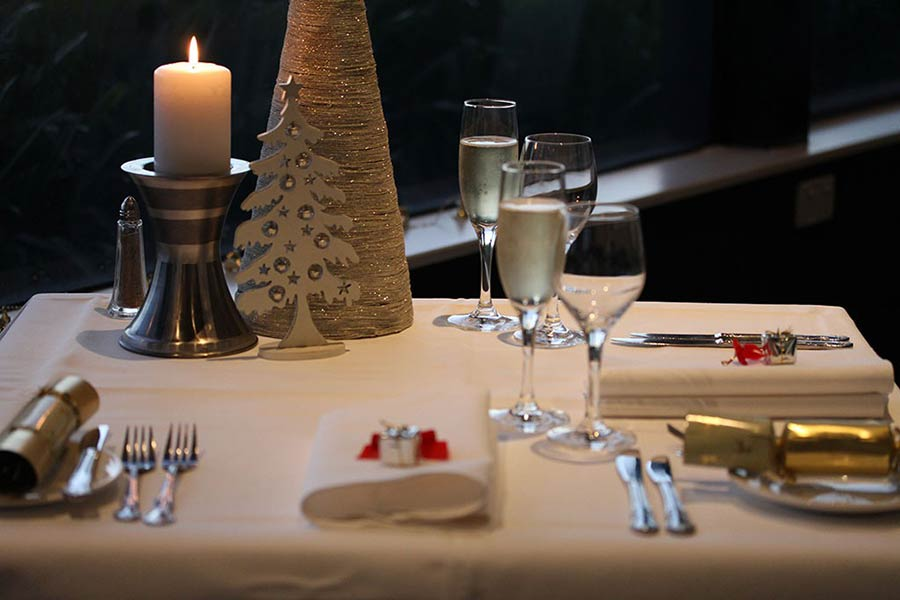 Photo of a candlelit table decorated in a Christmas theme
