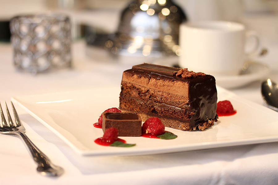 Slice of chocolate cake on a white plate with strawberries