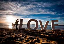 Bride and groom in the sunset at Brighton Beach next to letters which spell LOVE