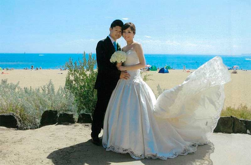 Photo of a bride and groom posing in front of Brighton Beach with the bride's dress flowing in the wind
