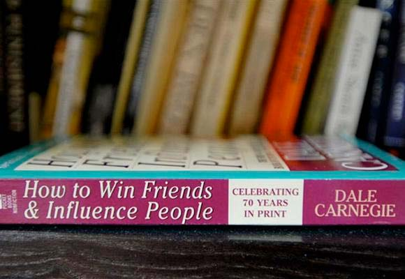 Copy of How to Win Friends & Influence People laying on it's side on a bookcase