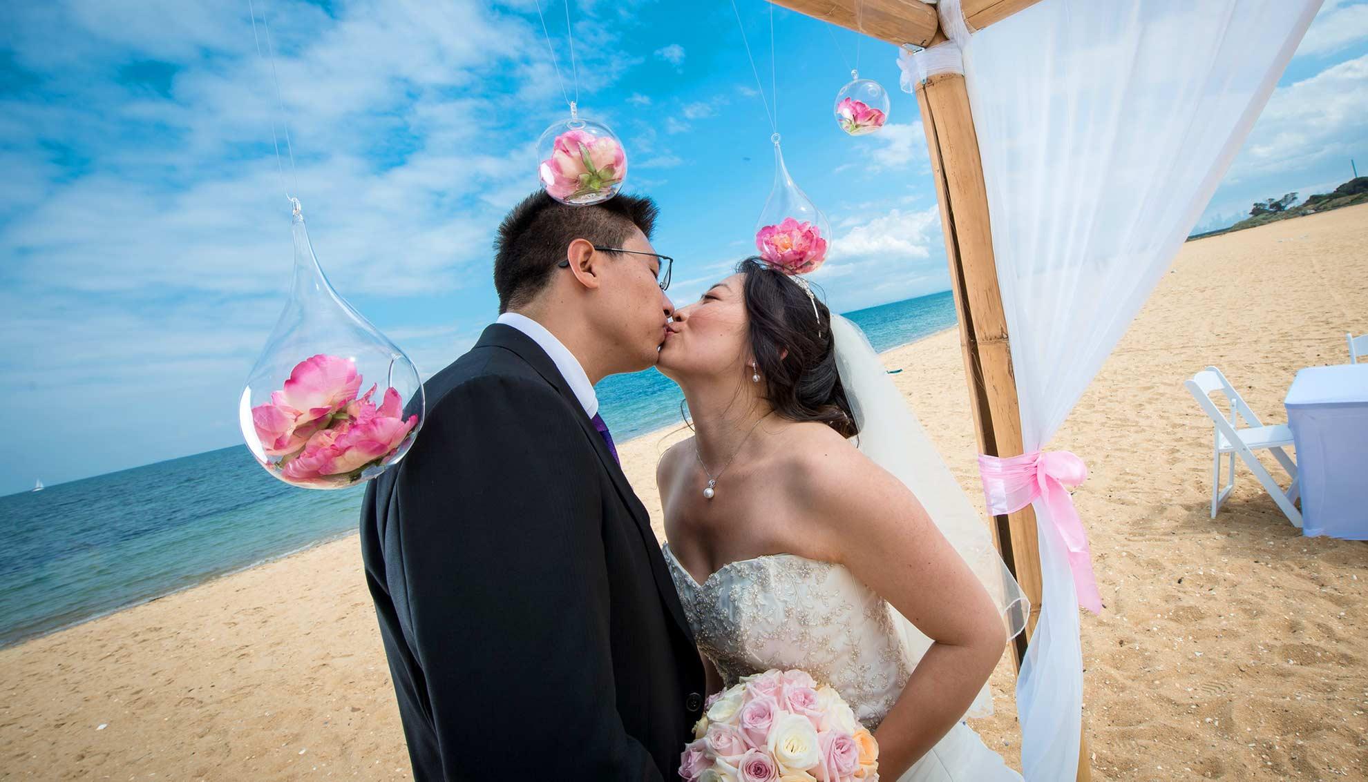 Bride and groom kissing under wedding arbor on Brighton Beach