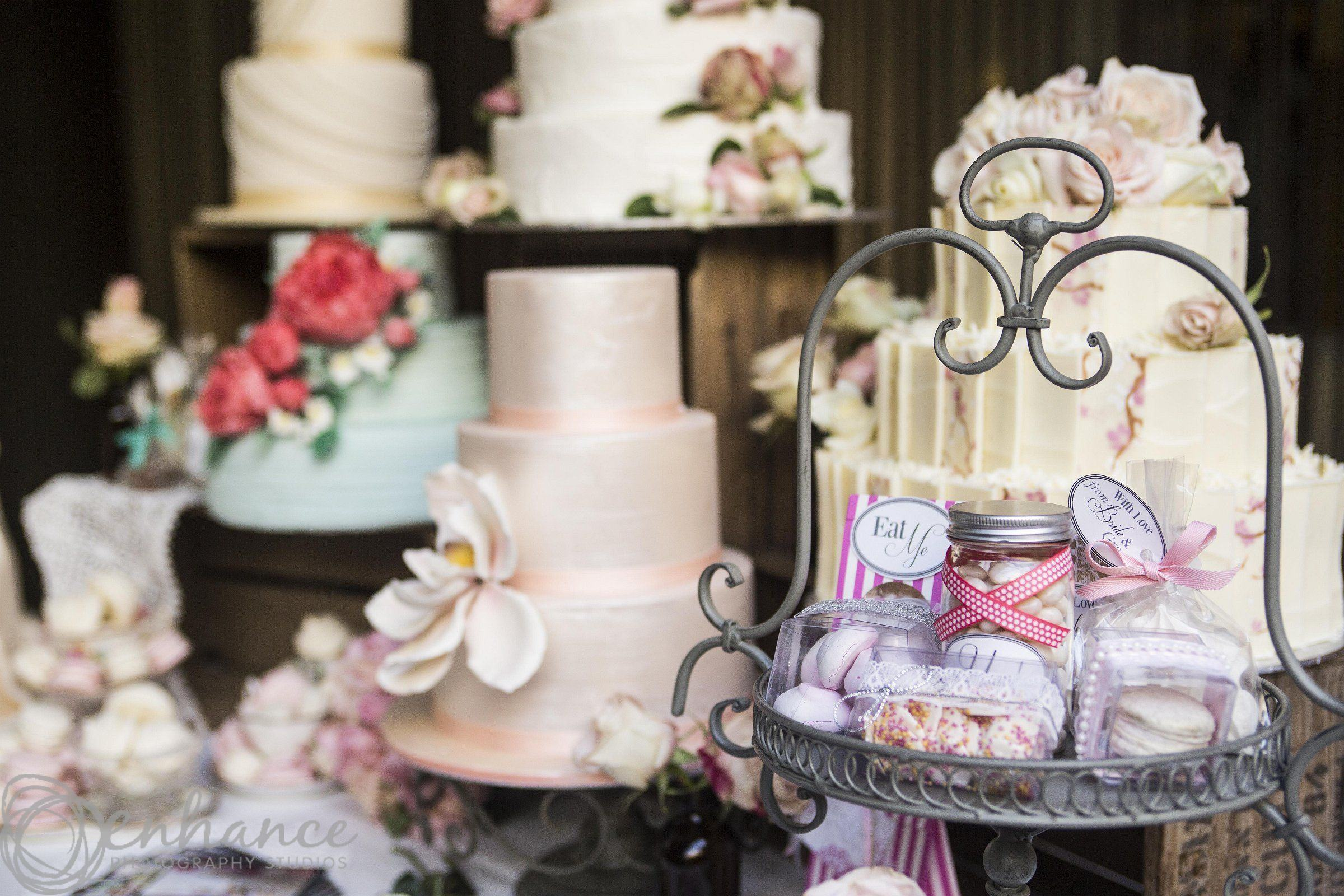 Photo of a wedding cake display, featuring wedding cakes in various colours and decorations