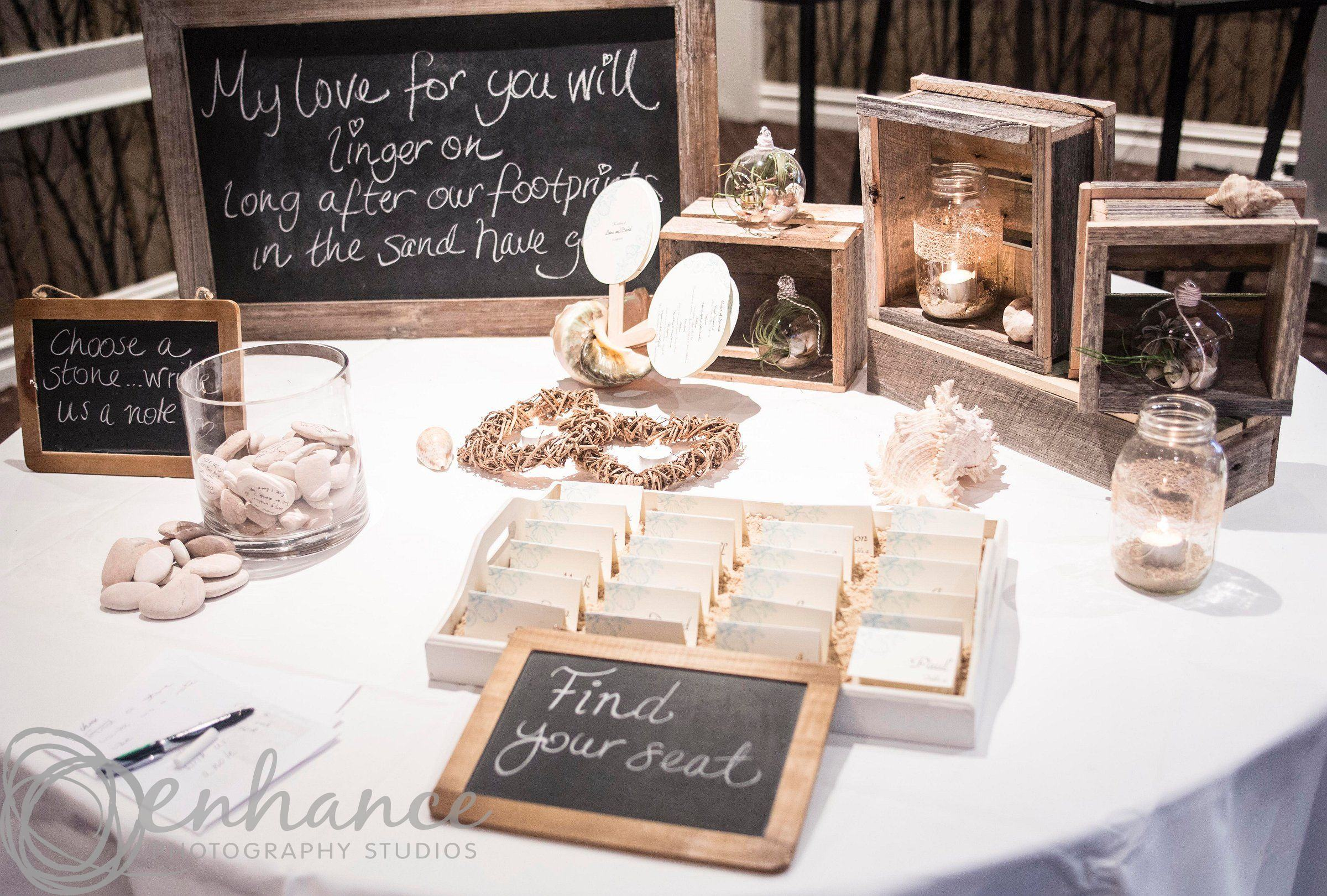 Photo of a wedding display featuring candles, pebbles and wooden boxes