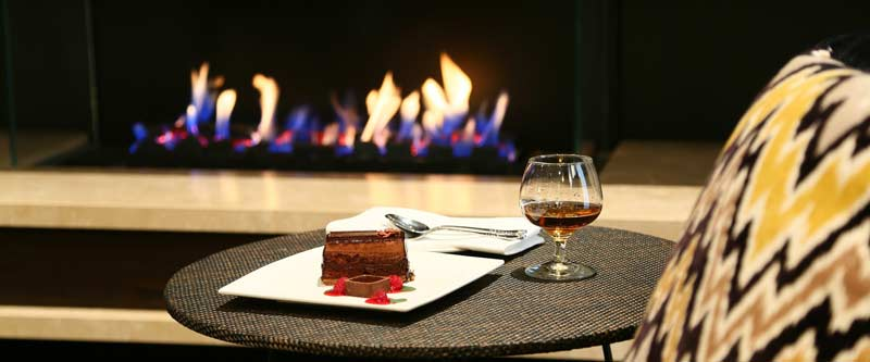 Photo of a glass of cognac and chocolate dessert by the fireplace