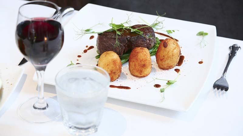 Formal dinner setting with a steak dish and glass of red wine